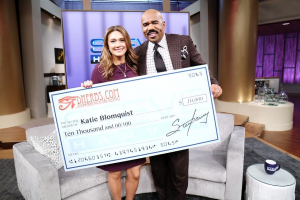 Student advocate, Katie Blomquist receives check from Steve Harvey.