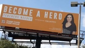 """Become a hero. Teachers needed."" billboard outside of UCF"