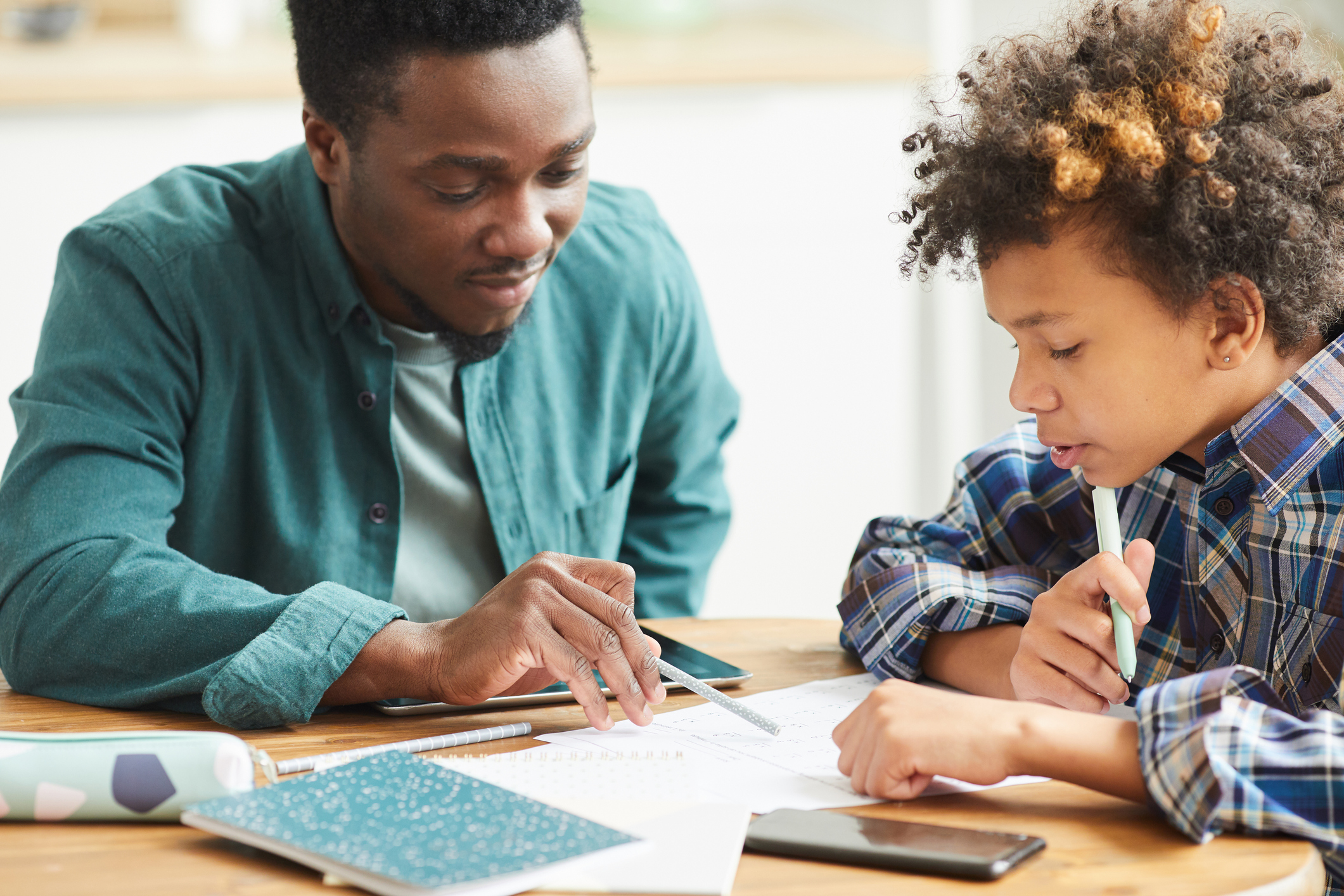 black male teacher helping young black student with school work